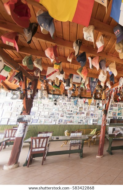 Kas, Turkey, May 8, 2016: Original interior of the cafe with lots of photos on the wall and flags and caps hanging on the ceiling