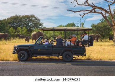 Kasane, Botswana - April 8, 2019 : Tourists observe and photograph a herd of elephants in front of a safari car in Chobe National Park