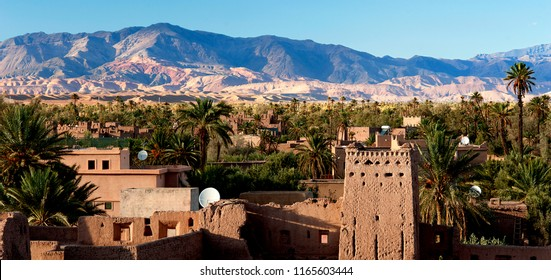Kasbah Amardil in Skoura, Morocco with the Atlas Mountains in the background and satellite dishes on the rooftops. It is one of Morocco's most famous Kasbahs, or fortress-palaces.