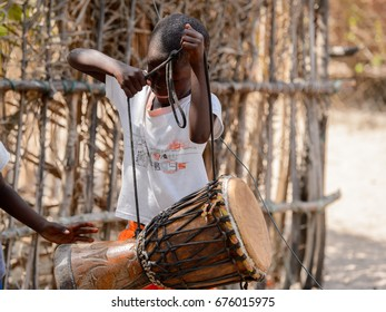 KASCHOUANE, SENEGAL - APR 29, 2017: Unidentified Diola boy carries a drum in Kaschouane village. Diolas are the ethnic group predominate in the region of Casamance