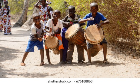KASCHOUANE, SENEGAL - APR 29, 2017: Unidentified Diola little boys play the drums in Kaschouane village. Diolas are the ethnic group predominate in the region of Casamance