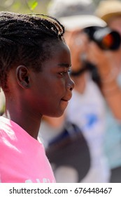 KASCHOUANE, SENEGAL - APR 29, 2017: Unidentified Diola girl with braids in pink shirt walks in Kaschouane village. Diolas are the ethnic group predominate in the region of Casamance