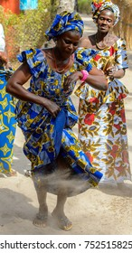 KASCHOUANE, SENEGAL - APR 29, 2017: Unidentified Diola woman in national colored clothes and headscarf makes a traditional Essipati dance in Kaschouane village.