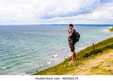 Kaseberga, Sweden - August 1, 2016: Man standing on seaside hilltop taking a landscape photograph with his mobile phone. Real life situation.