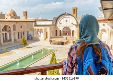 Kashan, Iran - 21 October, 2018: Female tourist enjoying view of traditional Iranian courtyard with pool and fountains from balcony at Tabatabaei Historical House. Awesome Persian exterior.