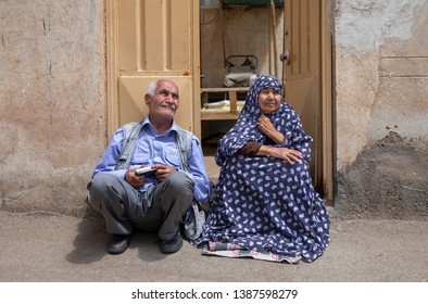 Kashan, Iran, 26th April 2019: old iranian couple resting at their doorstep in a village in IRan