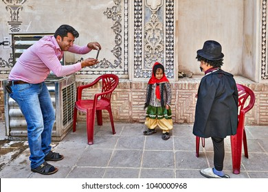 Kashan, Iran - April 26, 2017: Iranian man takes pictures of his children in traditional clothes in Tabatabaei historical house.