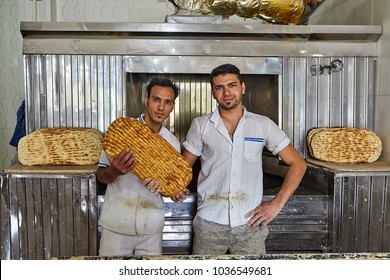 Kashan, Iran - April 27, 2017: Two young bakers demonstrates Iranian flat bread barbari while inside bakehouse.