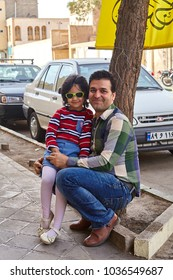 Kashan, Iran - April 27, 2017: A little girl in sunglasses, and a young man, her father, posing for a photo on a city street.