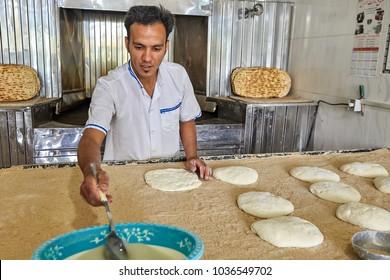 Kashan, Iran - April 27, 2017: Prepared Iranian flat bread named barbari, Baker kneading dough at counter.