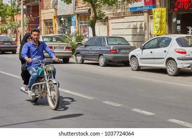 Kashan, Iran - April 27, 2017:  young muslim man and a woman in a hijab ride a motorcycle.
