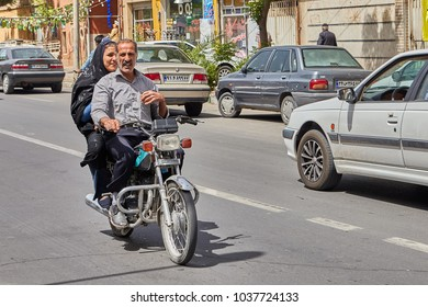 Kashan, Iran - April 27, 2017: Muslim couple - a man and a woman in a hijab ride a motorcycle on a busy street.