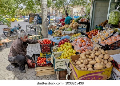Kashan, Iran - April 27, 2017: A street vendor of vegetables and fruits arranges merchandise in his stall.