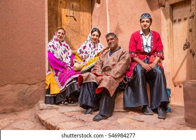 KASHAN, IRAN - MAY 2, 2015: a family in traditional clothes in the ancient village of Abyaneh, near Kashan, in Iran. In background, the typical red mud-brick houses of Abyaneh.