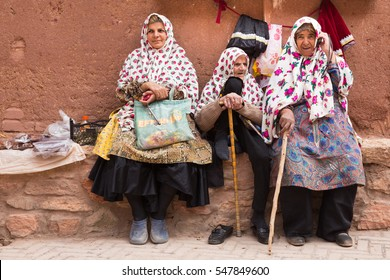 KASHAN, IRAN - MAY 2, 2015: some women in the ancient village of Abyaneh, near Kashan, in Iran. In background, the typical red mud-brick houses of Abyaneh.