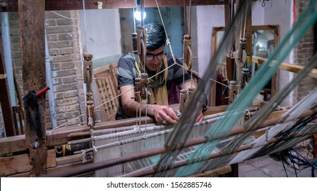 Kashan, Iran - May 2019: Iranian man crafting a wool carpet on the cotton strings in the carpet workshop