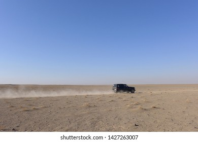 Kashan, Iran - October 2017 : A 4-wheels car driving in a desert creating a dust trail near Kashan, Iran.