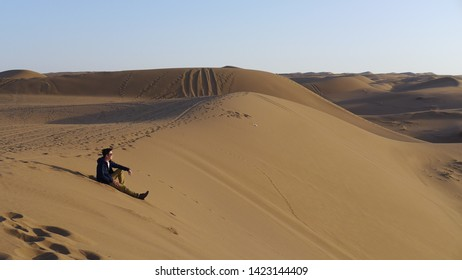 Kashan, Iran - October 2017 : A man sitting and posing for picture on a large sand dune near Kashan, Iran.