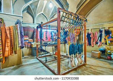 KASHAN, IRAN - OCTOBER 22, 2017: The traditional textile workshop, offering fabrics, clothes and accessories is located in Abbasi House and decorated with wooden hand loom, on October 22 in Kashan.