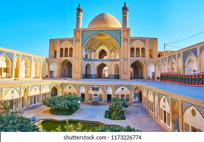 KASHAN, IRAN - OCTOBER 22, 2017: The scenic courtyard of Agha Bozorg Mosque with bright blue tiled patterns on walls and iwan (portal) and the green garden with fountain, on October 22 in Kashan.