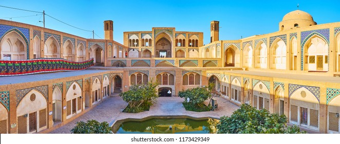 KASHAN, IRAN - OCTOBER 22, 2017: Panorama of Agha Bozorg mosque with garden and madrasah on the ground floor, the beautiful portal and badgirs (wind towers) on the upper floor, on October 22 in Kashan