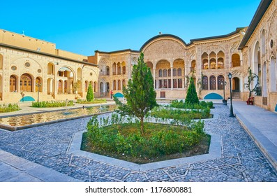 KASHAN, IRAN - OCTOBER 22, 2017: The nice ornamental garden of Tabatabaei House with fountain amid the small trees and picturesque summer terrace on background,  on October 22 in Kashan.