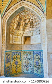 KASHAN, IRAN - OCTOBER 22, 2017: The richly decorated mihrab of Agha Bozorg mosque with painted arabesques, Islamic calligraphy, carved muqarnas details and Persian tilework, on October 22 in Kashan.