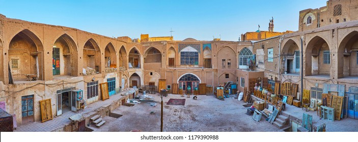 KASHAN, IRAN - OCTOBER 22, 2017: Courtyard of old caravanserai with warehouses of Grand Bazaar stores, the antique pieces of furniture stand in the street and wait for repair, on October 22 in Kashan.