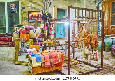 KASHAN, IRAN - OCTOBER 22, 2017: Traditional hand-loom with examples of natural fabrics in front of textile store in Aminoddole Caravanserai of the Grand Bazaar, on October 22 in Kashan.