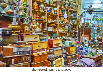 KASHAN, IRAN - OCTOBER 22, 2017: The heaps of vintage pieces - radios, tableware, statuettes, samovars, coffee pots and kerosene lamps in antique shop of the Grand Bazaar, on October 22 in Kashan.