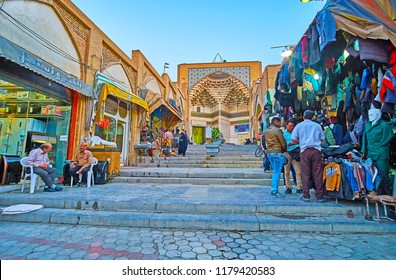 KASHAN, IRAN - OCTOBER 22, 2017: The market street of Grand Bazaar with a view on portal of Mir Emad (Meidan) Mosque, decorated with muqarnas details and tiled patterns, on October 22 in Kashan.