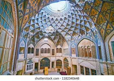 KASHAN, IRAN - OCTOBER 22, 2017: Historic court of Hajj Seyed Hossein Sabbaq Timcheh Caravanserai of Grand Bazaar with richly decorated vault and stores on different floors, on October 22 in Kashan.