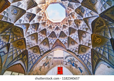 KASHAN, IRAN - OCTOBER 22, 2017: The cupola of small court of Hajj Seyed Hossein Sabbaq Timcheh Caravanserai of Grand Bazaar with colorful arabesques and muqarnas plasterwork, on October 22 in Kashan.