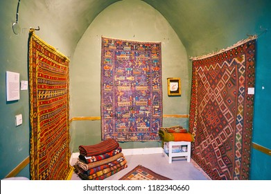 KASHAN, IRAN - OCTOBER 22, 2017: Unusual Baluch war carpet from Afghanistan with tanks, helicopters, missiles and soldiers in antique rug store of Grand Bazaar, on October 22 in Kashan.