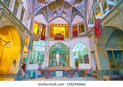 KASHAN, IRAN - OCTOBER 22, 2017: The small trading dome of Hajj Seyed Hossein Sabbaq Timcheh caravanserai of Grand Bazaar with rug stores and cafe on the underground floor, on October 22 in Kashan.