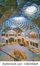 KASHAN, IRAN - OCTOBER 22, 2017: Interior of splendid Hajj Seyed Hossein Sabbaq Timcheh Caravanserai, preserved in Grand Bazaar and decorated with honeycomb vault and mosaic, on October 22 in Kashan.