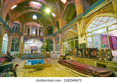KASHAN, IRAN - OCTOBER 22, 2017: The carpet shops in medieval caravanserai of Grand Bazaar, decorated with muqarnas dome and painted arabesques, on October 22 in Kashan.