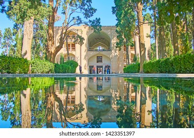 KASHAN, IRAN - OCTOBER 23, 2017: The main pool of Fin Garden with reflected arched pavilion of Kushak (pool house), surrounded by lush greenery, on October 23 in Kashan.