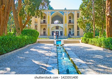 KASHAN, IRAN - OCTOBER 23, 2017: Walk along green shady alley of oldest in country Fin Garden with a view on Kushak - the scenic pool house, decorated with tiled patterns, on October 23 in Kashan.