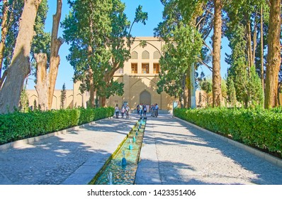 KASHAN, IRAN - OCTOBER 23, 2017: The tall shady trees of Fin Garden with a view on narrow fountain, entrance gate and rampart wall, on October 23 in Kashan.