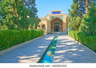 KASHAN, IRAN - OCTOBER 23, 2017: The facade of Fin Garden museum behind the shady alley with water stream, on October 23 in Kashan.