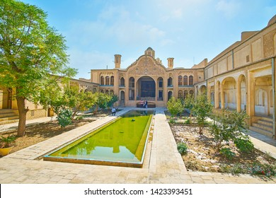 KASHAN, IRAN - OCTOBER 23, 2017: The ornate courtyard of Borujerdi Historical House with fountain, green garden and richly decorated walls and main portal (iwan), on October 23 in Kashan.