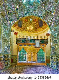 KASHAN, IRAN - OCTOBER 23, 2017: The prayer hall of Imamzadeh Ibrahim Mausoleum with sarcophagus, surrounded by ornate mirrorwork, painted and tiled patterns, on October 23 in Kashan.