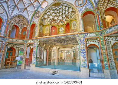 KASHAN, IRAN - OCTOBER 23, 2017: The richly decorated hall of Borujerdi Historical House with carved and painted patterns, muqarnas details in niches and on dome, on October 23 in Kashan.