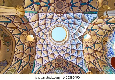 KASHAN, IRAN - OCTOBER 23, 2017: The intricate inner dome of Borujerdi Historical House with stucco muqarnas, painted patterns and light hole in the middle, on October 23 in Kashan.