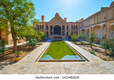KASHAN, IRAN - OCTOBER 23, 2017: Birouni (exterior) of Borujerdi Historical House with splendid carved patterns of walls and rectangular fountain amid the garden, on October 23 in Kashan.