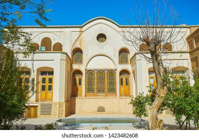 KASHAN, IRAN - OCTOBER 23, 2017: The beautiful portal of small courtyard of Borujerdi Historical House with stained-glass windows and fine ornaments on plaster wall, on October 23 in Kashan.