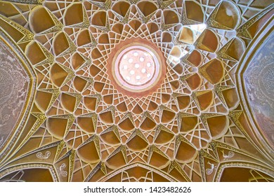 KASHAN, IRAN - OCTOBER 23, 2017: The scenic dome of the entrance gate of Borujerdi Historical House with muqarnas (honeycomb) decoration around the light hole, on October 23 in Kashan.