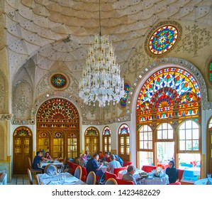 KASHAN, IRAN - OCTOBER 23, 2017: Interior of Sadeghi Traditional House restaurant, located in white hall with carved and mirror patterns, colorful stained glass windows, on October 23 in Kashan.