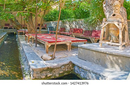 KASHAN, IRAN - OCTOBER 23, 2017: Relax in shady tea house with comfortable trestle beds, standing along the water stream, providing fresh cool air, on October 23 in Kashan